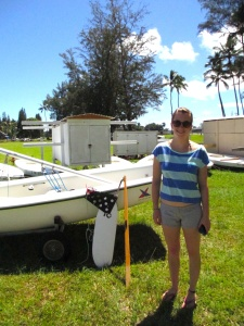 Emily Schneider, double major from Alaska, stands in front of a sailboat at Hilo Bayfront.